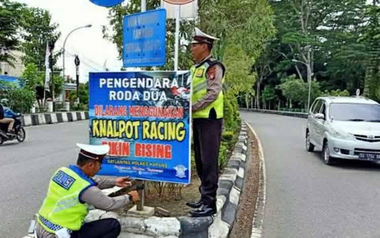 Personel Sat Lantas Polres Kapuas memasang imbauan tertib berlalu lintas di wilayah setempat.