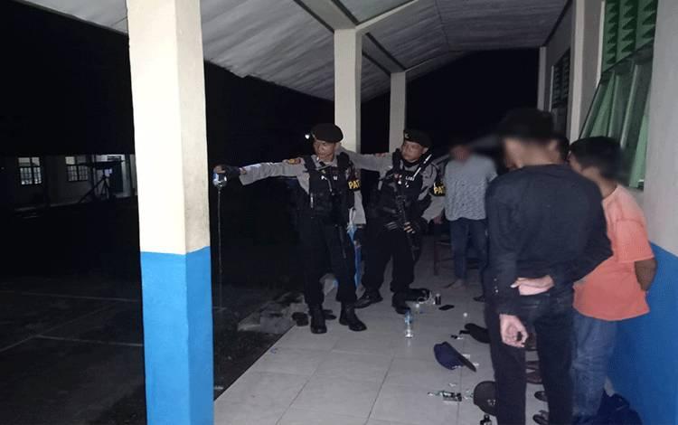 Anggota Sabhara Polres Barito Timur merazia sekumpulan pelajar yang pesta miras di halaman sekolah.
