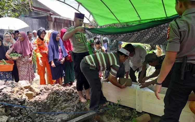 Kapolsek Jaya Karya, Ipda Doohan Octa Prasetya peci hitam, saat membantu pemakaman korban tewas tenggelam, Selasa, 10 Maret 2020.