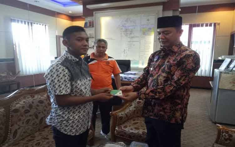 Bupati Sukamara, Windu Subagio menyerahkan kartu perlindungan jaminan sosial kepada atlet yang mengikuti seleksi Timnas Pelajar U-15
