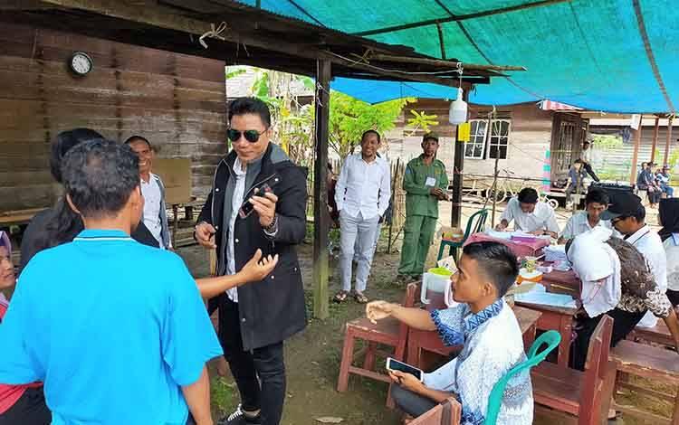 Bupati Kotim Supian Hadi berbincang dengan warga di TPS di dalah satu desa di Kecamatan Cempaga saat memantau pelaksanaan Pilkades Sabtu, 14 Maret 2020