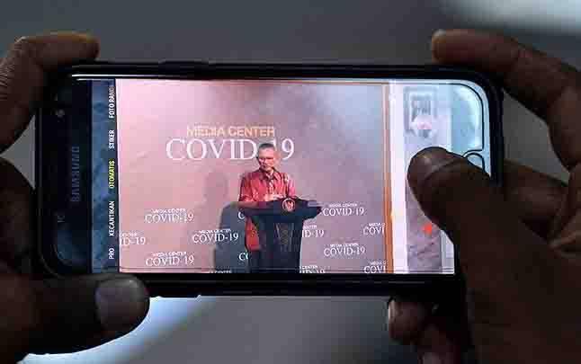 Seorang wartawan merekam juru bicara pemerintah untuk penanganan COVID-19 Achmad Yurianto saat memberikan keterangan pers di Kantor Presiden, Jakarta, Rabu, 11Maret 2020. (foto : ANTARA via teras.id)