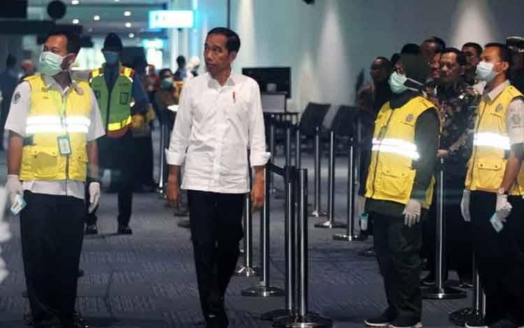 Presiden Joko Widodo (tengah) mencoba thermal scanner yang dipasang di terminal kedatangan luar negeri saat melakukan peninjauan kesiapan Bandara dalam menghadapi COVID-19 di Terminal 3 Bandara Soekarno Hatta, Tangerang, Banten, Jumat (13/3/2020). ANTARA FOTO/Muhammad Iqbal/pd/pri.