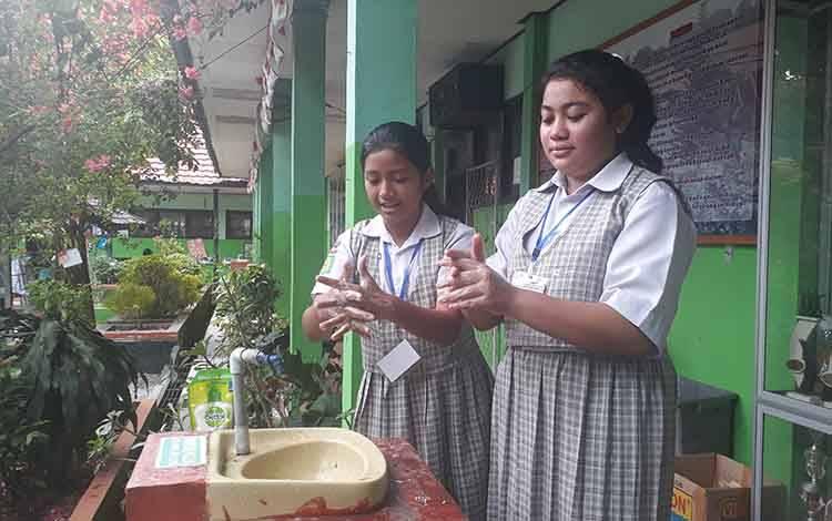Pelajar Kelas VI SDN 1 Sidorejo Mustika Perwita (12) danNabilla Irda Andini (12), saat memperagakan cara cuci tangan yang baik dan benar. Keduanya merasa belajar di sekolah lebih menyenangkan dari pada dirumah.