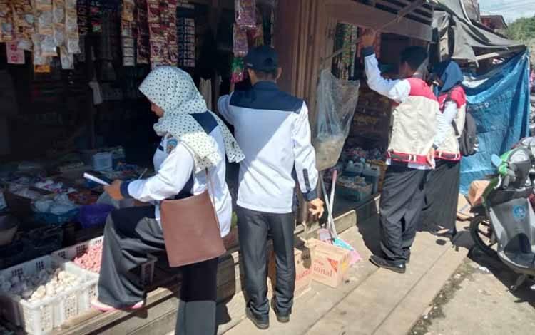 Petugas dari Disperindagkop dan UKM Kabupaten Mura ketika melakukan pengecekan harga barang di pasar Pelita Hilir, Puruk Cahu, Senin 23 Maret 2020.