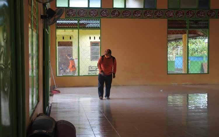 Salah seorang anggota BPBD Barsel menyemprotkan disinfektan di salah satu masjid.