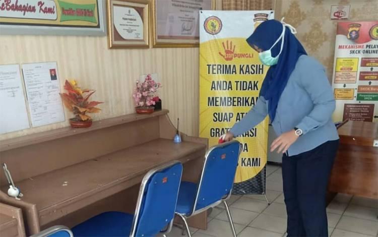 Petugas layanan SKCK Polres Kobar menyemprotkan cairan disinfektan