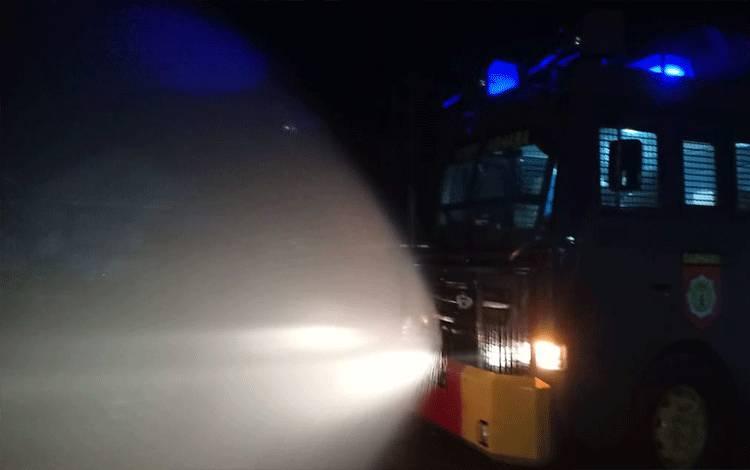 Polres Kotim lakukan penyemprotan disinfektan di jalan raya Kota Sampit gunakan mobil AWC, Selasa malam, 24 Maret 2020.