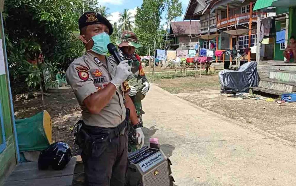 Personel TNI Polri memberikan imbauan kepada masyarakat di Murung Raya, untuk bersama-sama mencegah virus corona.