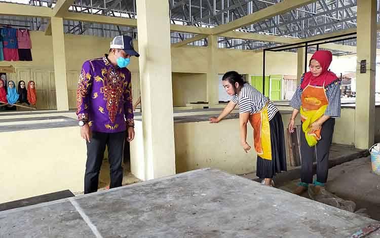 Bupati Kotim Supian Hadi saat berbincang dengan pedagang di Pasar Keramat Sampit. Sementara, pedagang pasar dadakan disiapkan lapak di parkiran Pusat Perbelanjaan Mentaya (PPM) Sampit, Kamis, 26 Maret 2020.