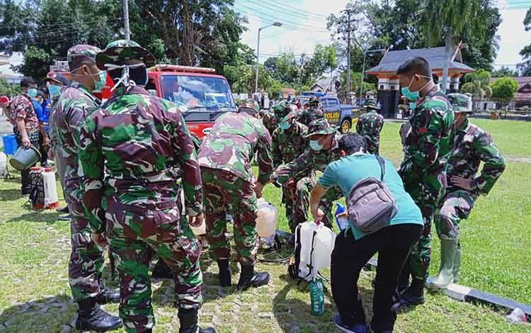 Anggota TNI dan petugas pemadam kebakaran yang tergabung dalam Gugus Tugas Penanggulangan Covid-19 bersiap melakukan penyemprotan disinfektan.