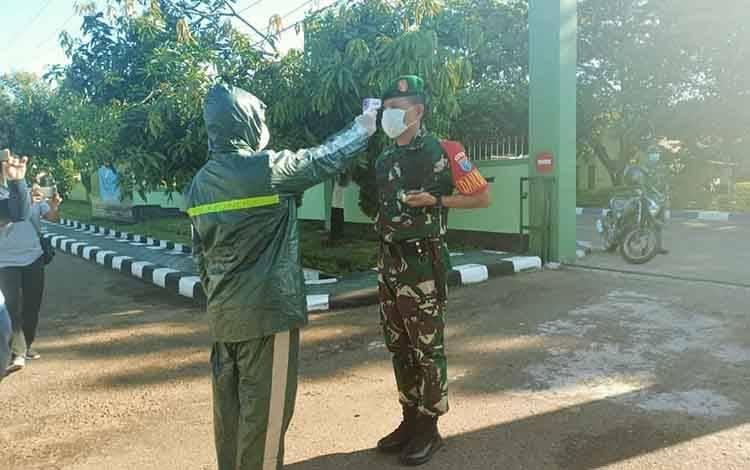Dandim 1013 Muara Teweh, Letkol Inf Yusan Riawan saat diperiksa suhu tubuh saat memasuki areal Makodim 1013 Muara Teweh.