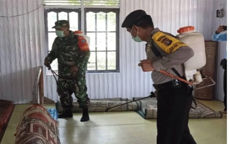Anggota Polsek Marikit dan anggota TNI menyemprotkan cairan disinfektan di fasilitas umum di Tumbang Hiran.