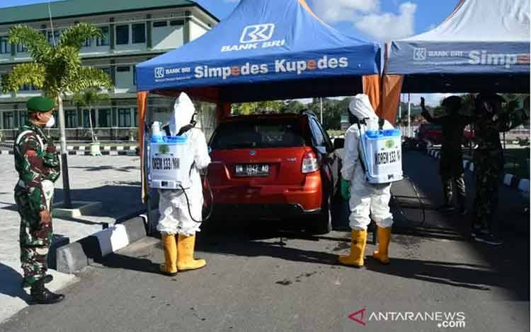 Personel TNI dan Polri menyemprotkan cairan disinfektan di halaman Makorem 133/Nani Wartabone, di Kabupaten Gorontalo, Gorontalo, Kamis (26/3/2020). ANTARA/HO