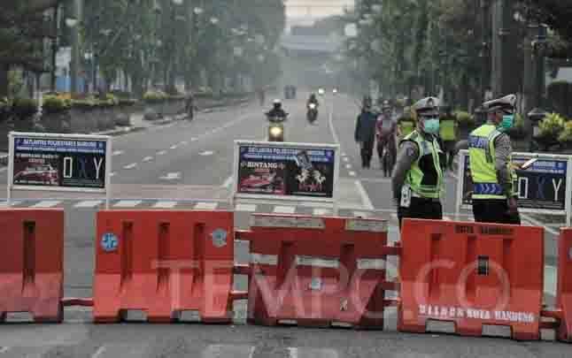 Polisi menutup akses sebagian ruas Jalan Asia Afrika untuk membatasi pergerakan kendaraan demi memutus penyebaran virus Corona, di Bandung, Jawa Barat, 29 Maret 2020. (foto : TEMPO.CO)