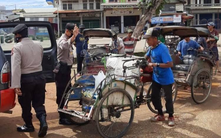 Pembagian paket sembako kepada tukang becak oleh anggota Polsek Dusun Tengah