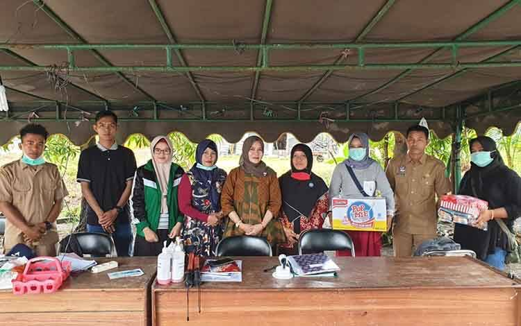 Ketua TP PKK Sukamara, Siti Zulaiha Windu Subagio saat menyerahkan bantuan makanan dan munuman kepada petugas posko pantau di pintu masuk wilayah Kabupaten Sukamara.