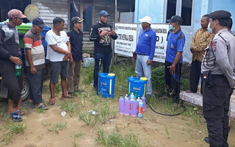 Anggota DPRD Kapuas Kunanto (tengah) saat menyerahkan bantuan cairan disinfektan di Desa Tamban Baru Timur.