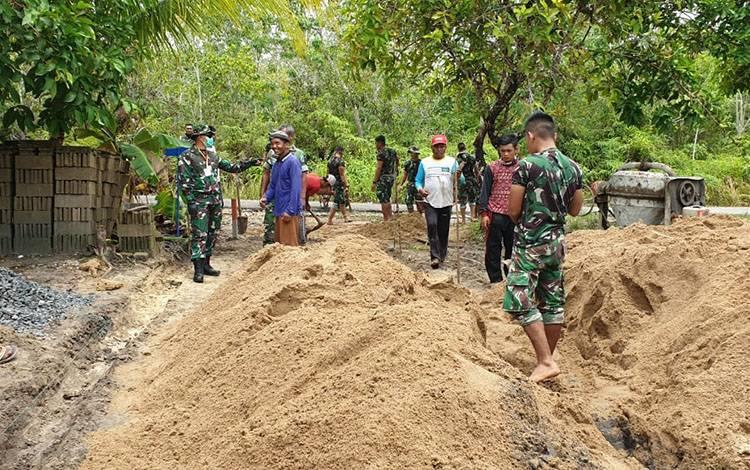 Dandim 1012 Buntok, Letkol Inf Tuwadi memimpin pengecoran jalan bersama masyarakat.