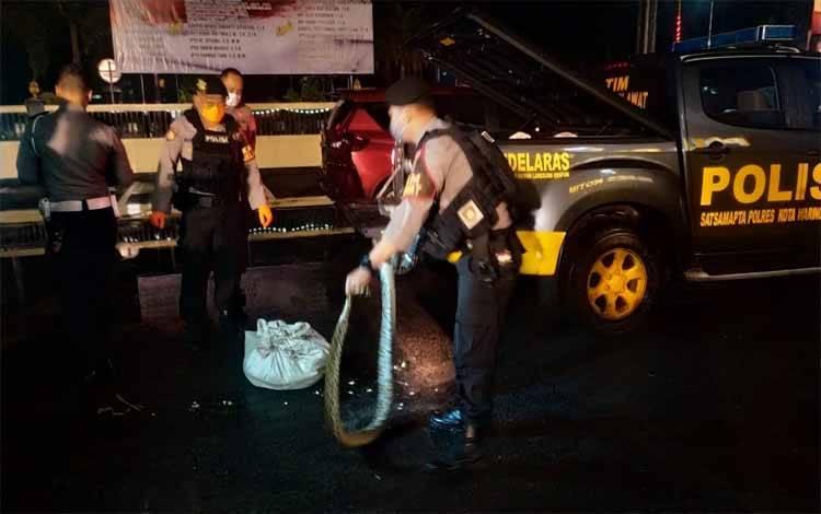 Warga bersama aparat kepolisian saat membuka tumpukan karung yang berisi ular python, 07 Maret 2020