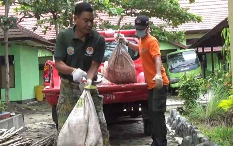 Komandan BKSDA Pos Jaga Sampit, Muriansyah menurunkan sejumlah karung berisi ular sanca kembang yang diserahkan kepolisian, Rabu 08 April 2020