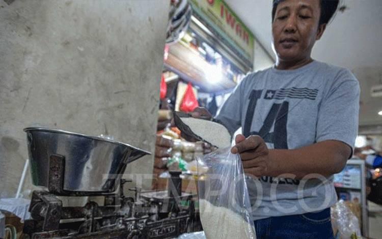 Pedagang menimbang gula pasir eceran di Pasar Senen, Jakarta, Senin, 16 Maret 2020. (foto : tempo.co)