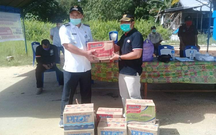 Anggota DPRD Kapuas Didi Hartoyo saat memberikan bantuan makanan untuk petugas Posko Pantau Covid-19 di Desa Pujon, Kecamatan Kapuas Tengah.