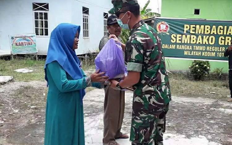 Pgs Dandim 1011 Kuala Kapuas Letkol Inf Ari Bayu Saputro saat membagikan sembako kepada warga di Desa Terusan Raya, Kecamatan Bataguh.