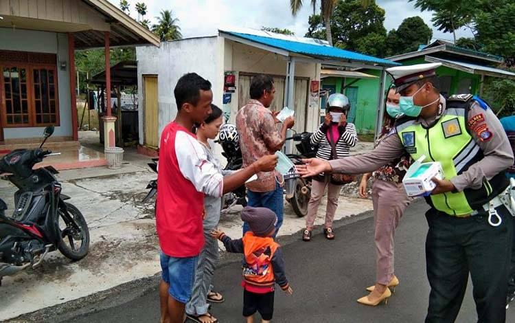 Anggota Satlantas Polres Pulang Pisau bersama Dinkes Kabupaten Pulang Pisau membagikan masker gratis kepada masyarakat dalam rangka pencegahan penyebaran virus corona, Kamis, 9 April 2020.
