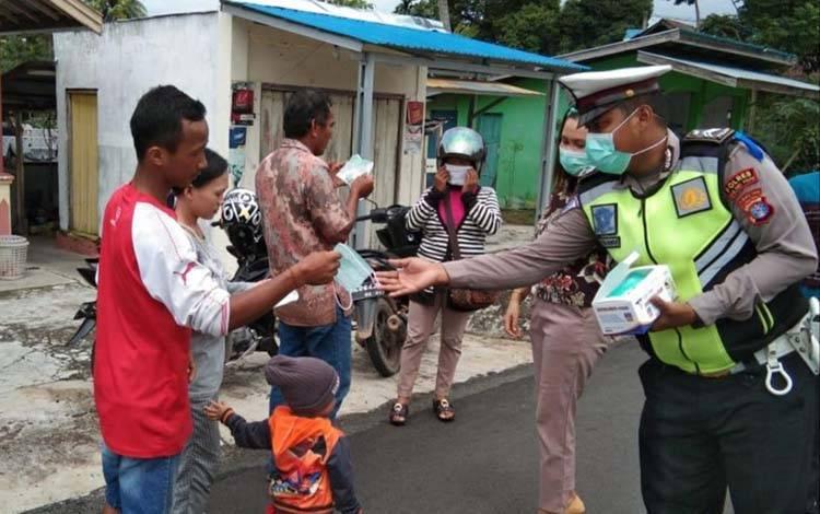 Anggota Satlantas Polres Pulang Pisau membagikan masker kepada masyarakat