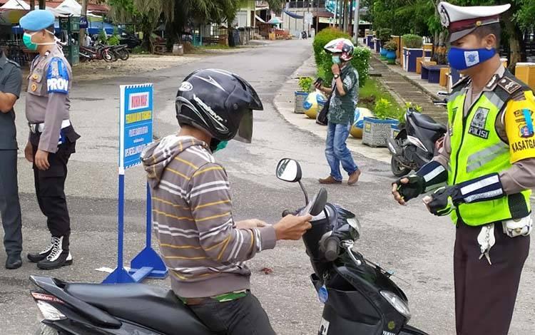Personel Satlantas Polres Barito Utara membagikan masker kepada pengendara roda dua yang melintas di Bundaran Buah Muara Teweh, Kamis, 9 April 2020.