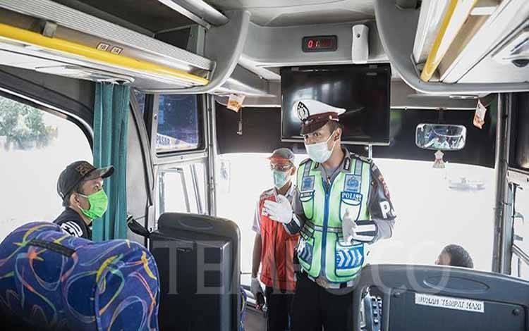 Petugas Kesehatan bersama Polisi melakukan pengecekan suhu tubuh penumpang Bus saat Check Point Pengawasan Pelaksanaan PSBB di Gerbang Tol Pasar Rebo 2, Jakarta, Jumat, 10 April 2020. (foto : tempo.co)