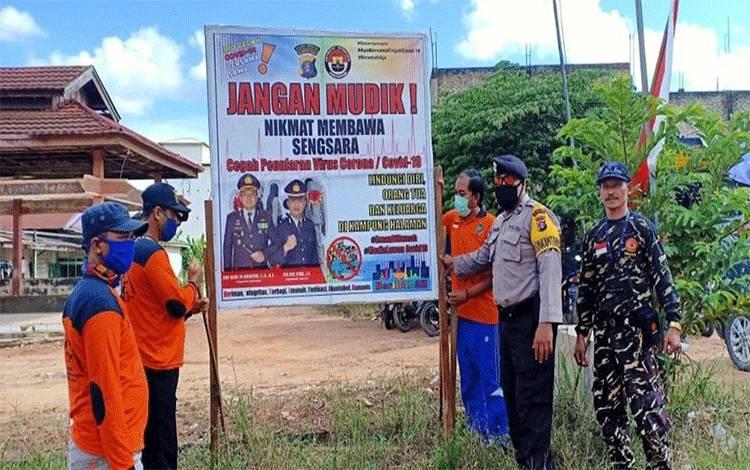 Anggota Polsek Hanau bersama petugas posko pemantauan Covid-19 Desa Rungau Raya memasang spanduk imbauan agar tidak mudik.