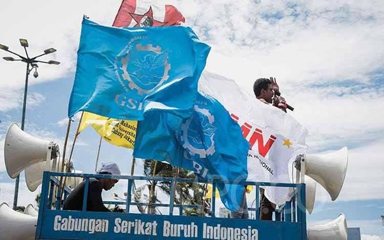 Massa gabungan Buruh dan Mahasiswa membentangkan spanduk saat menggelar aksi menolak omnibus law RUU Cipta Kerja di depan Gedung DPR RI, Jakarta, Senin, 9 Maret 2020. Dalam aksi ini massa menuntut pemerintah mjalankan segera Land Reform dan Industrialisasi Nasional. TEMPO/M Taufan Rengganis