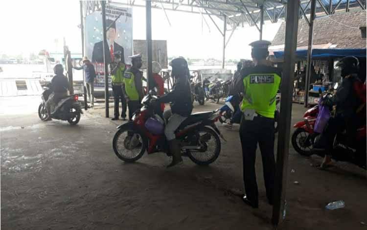 Personel Satlantas Polres Kapuas menyampaikan pesan keselamatan berlalulintas di pelabuhan feri penyeberangan