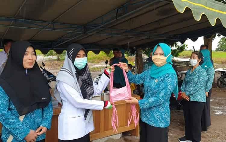 Ketua TP PKK Sukamara, Siti Zulaiha Windu Subagio saat menyerahkan masker kepada petugas kesehatan di posko pantau pintu masuk.