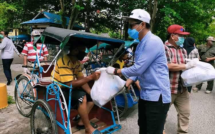 Bupati Kotim Supian Hadi bersama Sekda Kotim Halikinnor saat membagikan sembako untuk tukang becak dan tukang ojek di Sampit, Sabtu, 18 April 2020.