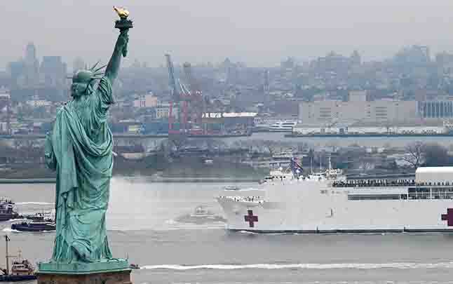 Kapal rumah sakit Angkatan Laut USNS Comfort melintas di dekat patung Liberty saat memasuki New York Harbor di New York City, AS, 30 Maret 2020. Pemerintah Amerika Serikat tidak hanya mempersiapkan USNS Comfort tetapi juga kepal rumah sakit Angkatan Laut USNS Mercy. (foto : REUTERS/Mike Segar via teras.id)