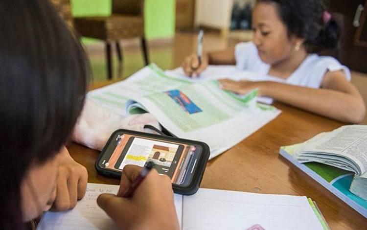 Dua anak menonton video belajar digital dari rumah di Bandung, Jawa Barat, Selasa 17 Maret 2020. Presiden Joko Widodo menegaskan bahwa kebijakan untuk bekerja, belajar dan beribadah di rumah perlu dilakukan untuk menekan penyebaran virus corona atau Covid-19. ANTARA FOTO/M Agung Rajasa