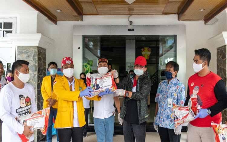 Agustiar Sabran menyerahkan sembako Rektor Universitas Palangka Raya, Andrie Elia dan perwakilan mahasiswa