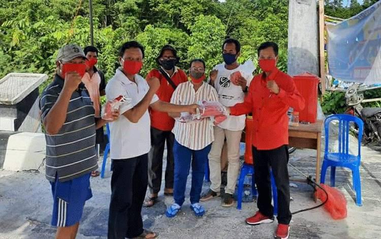 Anggota DPRD Kapuas Syarkawi H Sibu saat membagikan masker kain kepada masyarakat di wilayah hulu Kapuas, baru-baru ini.