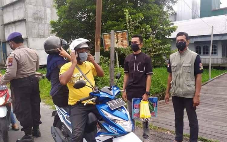 Relawan Gerakan Jaga Kampung (GJK) Kabupaten Sukamara membagikan masker kepada masyarakat