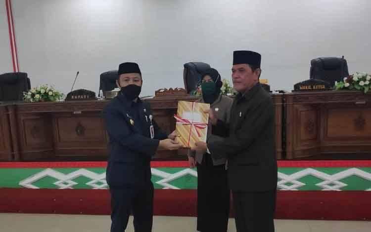 Bupati Barito Selatan, Eddy Raya Samsuri (kiri) menyerahkan LKPJ 2019 kepada Wakil Ketua DPRD, Yusuf Kalem, Rabu, 6 Mei 2020.