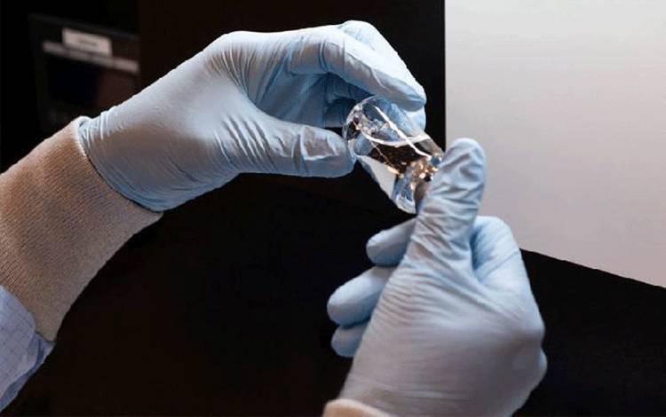 Seorang teknisi lab secara visual memeriksa botol berisi obat potensial virus corona remdesivir di fasilitas Ilmu Gilead di La Verne, California, AS 11 Maret 2020. [Gilead Sciences Inc / Handout via REUTERS]