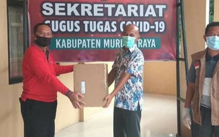 Penyerahan masker oleh Kepala Badan Keuangan dan Aset Daerah Kalteng H. Nuryakin kepada dr. Suria Siri Ketua Gugus Tugas Kabupaten Murung Raya