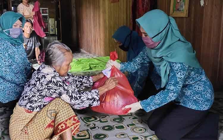 Ketua PKK Kabupaten Sukamara, Siti Zulaiha Windu Subagio saat menyerahkan bantuan kepada lansia yang ada di Kelurahan Padang.