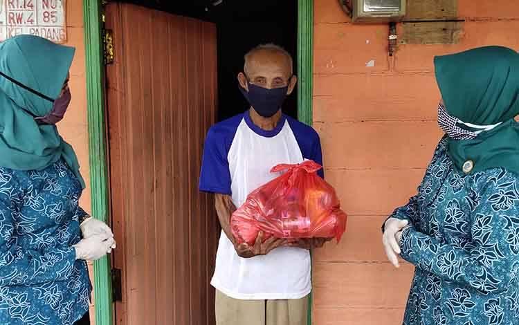 Ketua TP PKK Kabupaten Sukamara, Siti Zulaiha dan Ketua GOW Sukamara, Hj Hatmayanti Ahmadi saat menyerahkan bantuan kepada lansia di Kelurahan Padang.