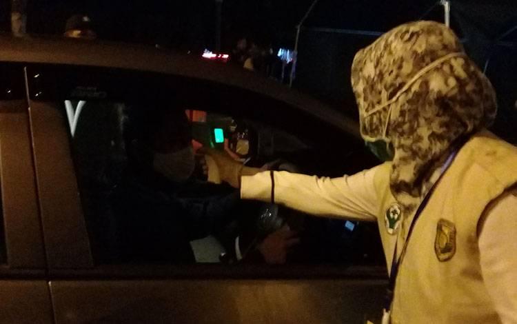 Tim Kesehatan dari Satgas Covid-19 Kota Palangka Raya saat melakukan pengecekan suhu tubuh pengguna Jalan yang melintas di pos cek poin Bundaran Besar, Selasa 12 Mei 2020 malam.