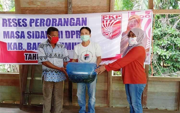 Rida Heriyani menyerahkan bantuan benih ikan saat kunjungan reses di Desa Pianggu