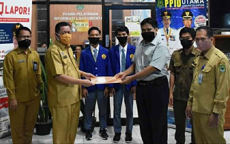 Penyerahan sertifikat oleh Kepala Dinas Kominfo Kapuas, Junaidi kepada perwakilan guru SMKN 1 Kuala Kapuas, Senin, 18 Mei 2020